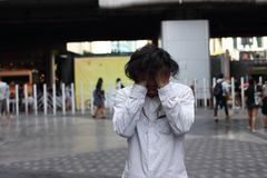 Niepokój stresujący się Azjatyckiego mężczyzny nakrywkowy czoło z rękami outdoors fotografia stock