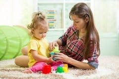 Niñera con el niño que juega en cuarto de niños Imágenes de archivo libres de regalías