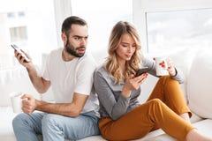 Nierad mężczyzna patrzeje jego żony indoors w domu używa telefon komórkowego fotografia stock