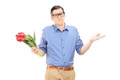 Nierad młody człowiek trzyma wiązkę kwiaty Zdjęcie Stock