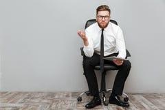 Nierad sfrustowany biznesmen trzyma komputer osobisty pastylkę w eyeglasses zdjęcia stock