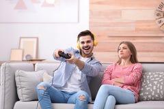 Nierada kobieta siedzi blisko jej mężczyzny bawić się gra wideo zdjęcie stock