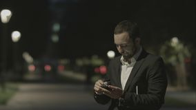 Nieradego brodatego biznesmena use mądrze telefon, podczas gdy stojący w miasto ulicie, biznesowego mężczyzna czytelnicze wiadomo Zdjęcia Stock