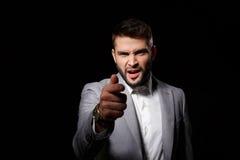 Nieradego młodego biznesmena ponting palec kamera nad czarnym tłem obraz stock
