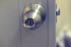 Nierdzewna drzwiowa gałeczka na białym drzwi Zdjęcie Stock