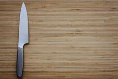 Nierdzewny kuchenny nóż na pustej tnącej desce obraz royalty free