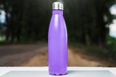 Nierdzewny termosu bidon na bielu stole, plenerowym Fiołkowy purpura kolor obrazy stock