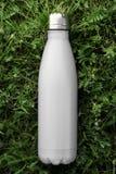 Nierdzewny termosu bidon odizolowywający na zielonej trawie plenerowej Biały matte kolor Pionowo fotografia bez skutków fotografia royalty free