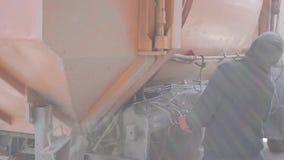 Nierozpoznany pracownika mężczyzna kontroluje śmieciarską maszynową pracę Pracownik w przypadkowych ubraniach używać grat maszynę zdjęcie wideo