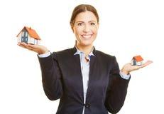 Nieruchomość makler trzyma dwa domu na ona ręka zdjęcie stock