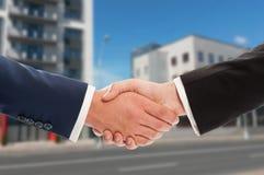 Nieruchomość uścisk dłoni nad nowym budynku tłem Obrazy Stock
