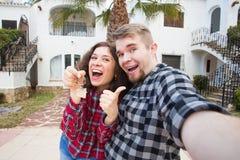 Nieruchomości i własności pojęcie - Szczęśliwi pary mienia klucze nowy dom i dom miniaturyzują obrazy royalty free