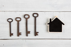 Nieruchomości pojęcie - mały dom i klucze na białym drewnianym biurku Obraz Royalty Free