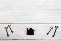 Nieruchomości pojęcie - mały dom i klucze na białym drewnianym biurku Obrazy Royalty Free