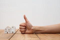 Nieruchomości pojęcie ręka pokazuje kciuk up przy miniatura domem Fotografia Royalty Free