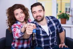 Nieruchomości pojęcie - szczęśliwi uśmiechnięci potomstwo pary seansu klucze Zdjęcia Stock