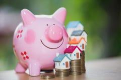 Nieruchomości sprzedaż, domowi oszczędzania, prosiątko bank, monety i dom, l fotografia stock