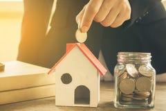 Nieruchomości inwestycja Dom i monety na stole Zdjęcia Stock