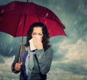 Niesende Frau mit Regenschirm Stockbild