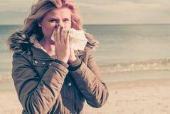 Niesende Frau in Taschentuch, äußerer sonniger Schuss Stockbild