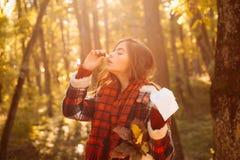 Niesendes junges M?dchen mit Nasenwischer unter gelben B?umen im Park Frau macht eine Heilung f?r die Erk?ltung Darstellen krank stockbilder