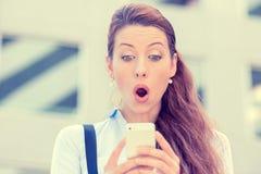 Niespokojna młoda dziewczyna patrzeje telefon widzii złą wiadomość lub fotografie z wstrętną emocją fotografia stock