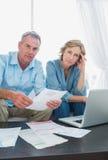 Niespokojna para płaci ich rachunki z laptopem patrzeje online Fotografia Stock