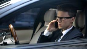 Niespokojnego biznesmena słuchająca zła wiadomość podczas gdy opowiadający na telefonie, nieudany kontrakt obraz royalty free