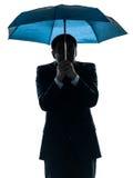 Niespokojny biznesowy mężczyzna pod parasolową sylwetką zdjęcie royalty free