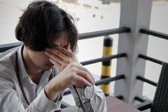 Niespokojny sfrustowany młody Azjatycki biznesowy mężczyzna bierze daleko szkła i zamyka jego oczy czuje napięcie lub próbuje i m fotografia stock