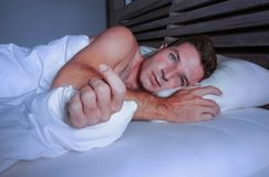Niespokojny zmartwiony młody atrakcyjny mężczyzna obudzony przy nocy lying on the beach na łóżkowy bezsennym z oka cierpienia sze Obraz Stock