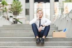 Niesprawiedliwy imbirowy młody dorosły pracownik siedzi na schodkach i zastanawiać się obraz royalty free