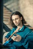 Niestaranny atrakcyjny młodego człowieka tonowanie zawiązuje na jego gitarze zdjęcie stock