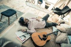Niestaranny ciemnowłosy męski muzyk odpoczywa w sypialni po powtórki fotografia royalty free