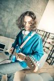 Niestaranny długowłosy mężczyzna inspiruje podczas gdy bawić się muzykę zdjęcie royalty free