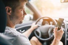 Niestaranny kierowca używa telefon komórkowego podczas gdy jadący fotografia stock