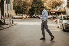 Niestaranny mężczyzna patrzeje telefon komórkowego podczas gdy krzyżujący ulicę zdjęcie royalty free