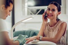 Niestaranny uśmiechnięty ciemnowłosy klient opowiada na smartphone zdjęcie stock