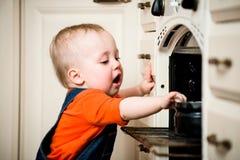 Niestrzeżony dziecko z otwartym piekarnikiem Zdjęcia Royalty Free