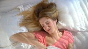 Nieszczęśliwa śpiąca młoda kobieta no chce budził się w ranku i chować pod koc zdjęcie wideo
