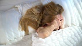 Nieszczęśliwa śpiąca młoda kobieta no chce budził się w ranku i chować pod koc swobodny ruch zbiory wideo