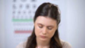 Nieszczęśliwa żeńska cierpienie migrena i zdejmować szkła, mylna obiektyw dioptra zbiory