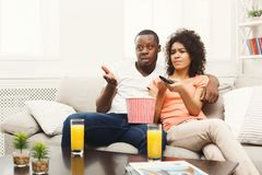 Nieszczęśliwa afroamerykańska potomstwo para ogląda TV w domu obrazy stock