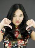 Nieszczęśliwa Azjatycka młoda kobieta daje kciukom zestrzela gest zdjęcia royalty free
