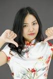 Nieszczęśliwa Azjatycka młoda kobieta daje kciukom zestrzela gest zdjęcie royalty free