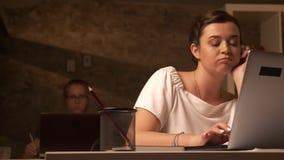 Nieszczęśliwa caucasian dziewczyna siedzi jeden zakup jeden z jej współpracownikiem i gapi się przy laptopem w ceglanym biurze