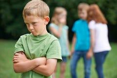 Nieszczęśliwa chłopiec Plotkuje Wokoło Innymi dziećmi Obrazy Stock