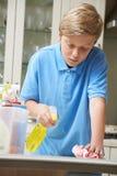 Nieszczęśliwa chłopiec Pomaga Czyścić dom zdjęcie royalty free