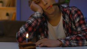 Nieszczęśliwa chłopiec w partyjnym kapeluszowym obsiadanie stole z tortem, odświętność urodziny samotnie zdjęcie wideo