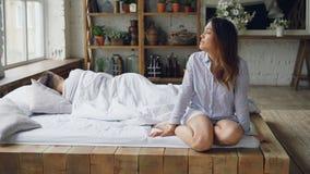 Nieszczęśliwa dziewczyna dotyka jej twarz i patrzeje okno jest siedząca na łóżku, płacz podczas gdy jej chłopak kłama w łóżku zdjęcie wideo